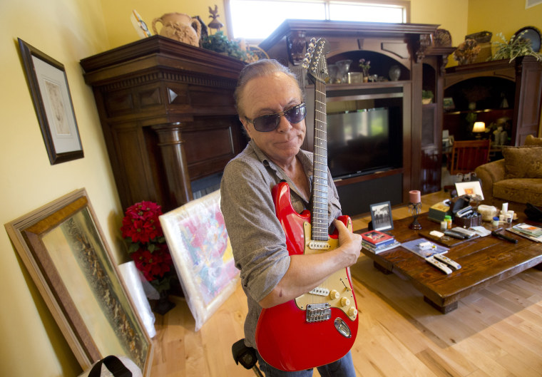 Image: David Cassidy holds one of his favorite guitars as he gives a tour of his five-bedroom Florida mansion in Fort Lauderdale, Florida