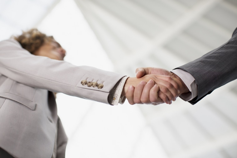 Image: Businessman and businesswoman shaking hands
