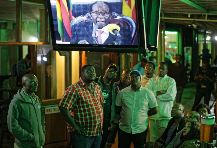 Image: Zimbabweans watch a televised address to the nation by President Robert Mugabe at a bar