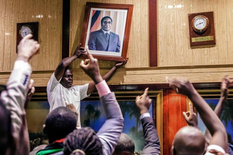 Image: People remove former Zimbabwean President Robert Mugabe's portrait  from the wall