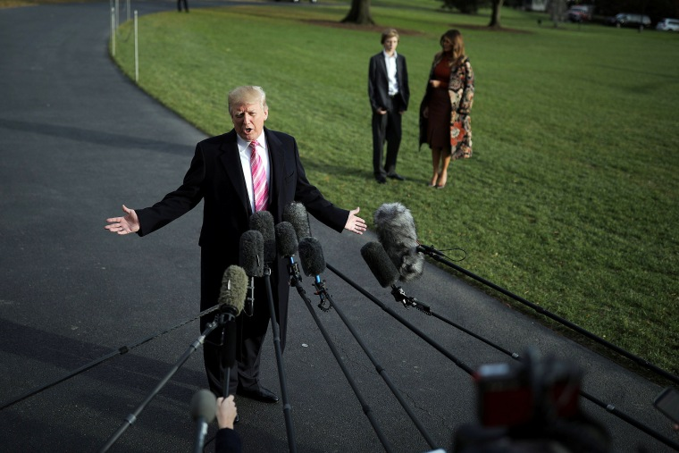 Image: U.S. President Donald Trump talks with the reporters as First Lady Melania Trump and her son Barron wait for him while departing the White House for Palm Beach, in Washington D.C.