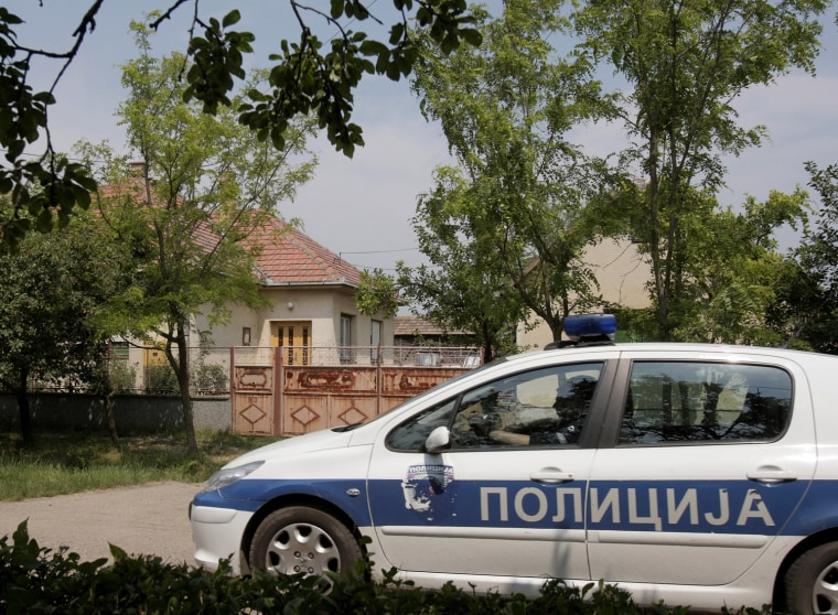 Image: A police car drives by the house, on left, where Ratko Mladic was found in the village of Lazarevo