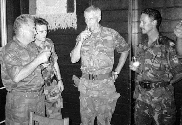 Image: Ratko Mladic, left, drinks a toast with Dutch U.N. Commander Tom Karremans
