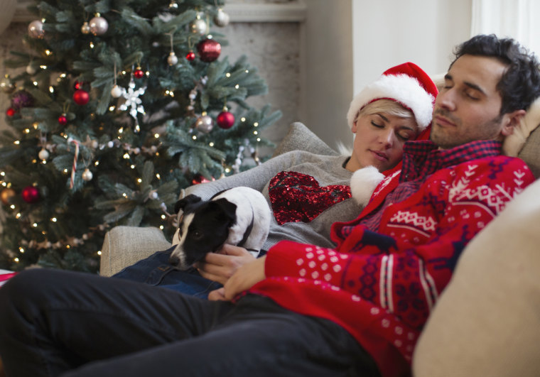 Serene couple napping with dog on sofa next to Christmas tree