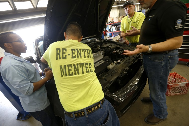 Image: Mentees work with mentors in the auto repair training shop inside the Louisiana State Penitentiary