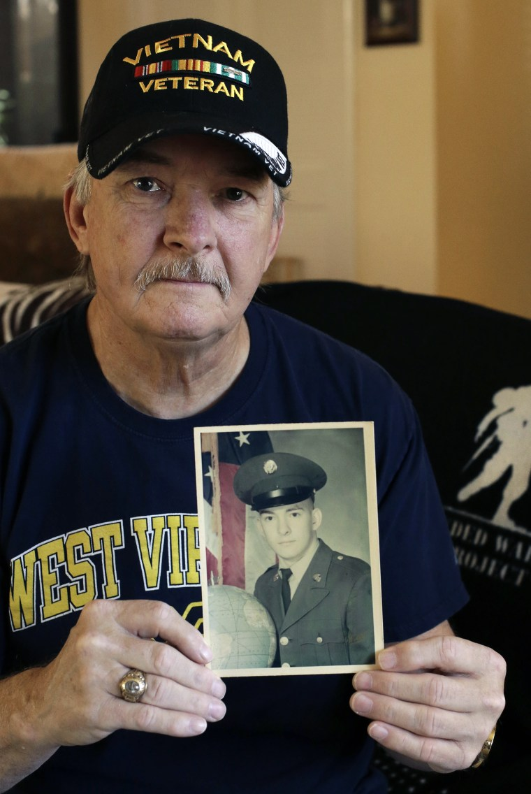 Image: Mike Baughman holds a 1971 photo of himself in his U.S. Army uniform at his home
