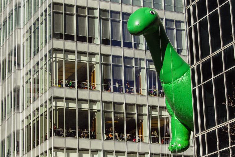 Image: People watch from windows as the Sinclair Dino balloon moves