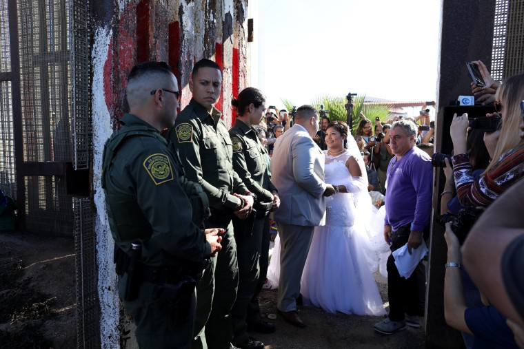 Image: U.S. resident Brian Houston marries Evelia Reyes as U.S. Border patrol agents open a single gate for in the border wall to allow selected families to visit along the U.S.-Mexico border in San Diego