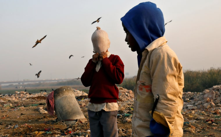 Image: A boy covers his face with a woollen hat on the banks of the Yamuna river in Delhi