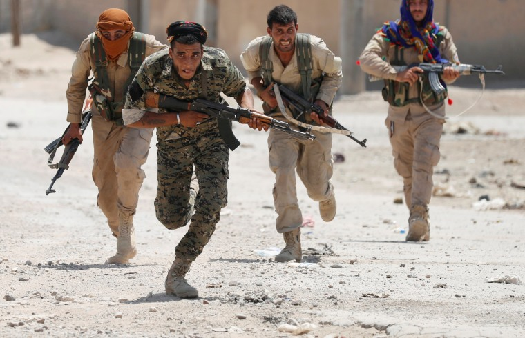 Image: Kurdish fighters from the People's Protection Units (YPG) run across a street in Raqqa, Syria