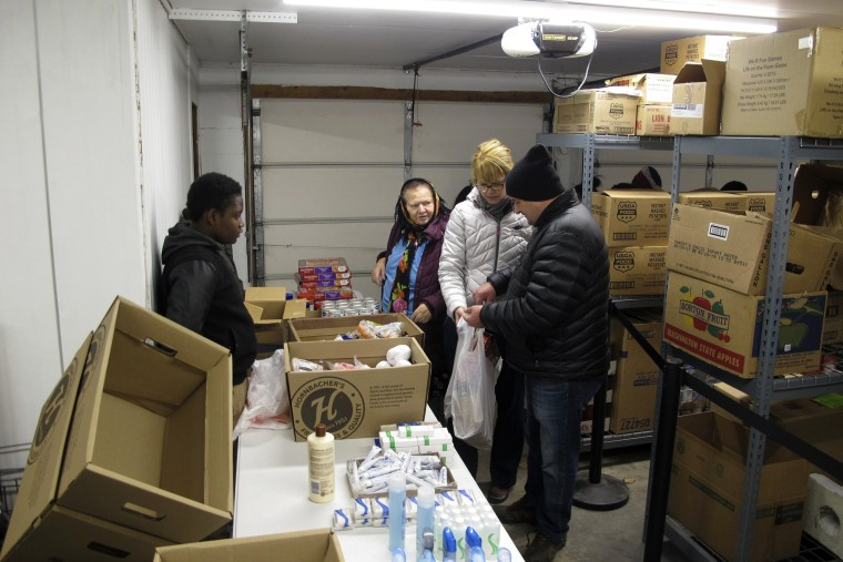 Image: Legacy Children's Foundation executive director Mary Jean Dehne, center, and Legacy student Joel Gama, left, help people pick out groceries at the foundation's food panty in Fargo, North Dakota, on Nov. 16, 2017.