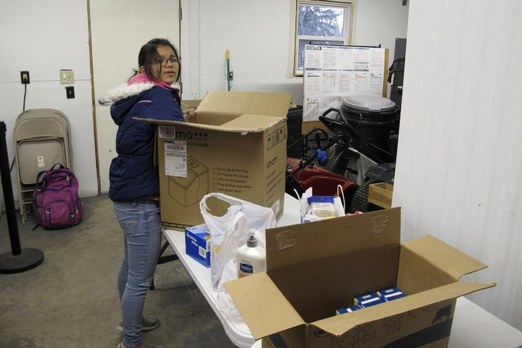 Image: Puja Chhertri, one of the organizers of the Legacy Children's Foundation food pantry in Fargo, North Dakota, unloads a box of supplies while setting up to hand out food and other goods on Nov. 16, 2017.