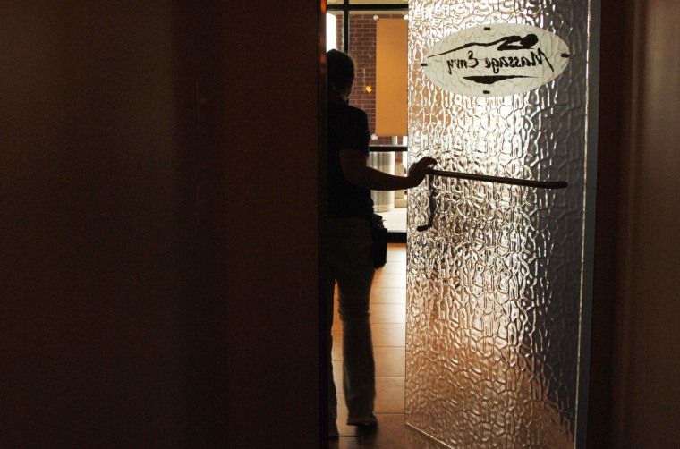 Image: A therapist walks through the entrance to the massage rooms at Massage Envy
