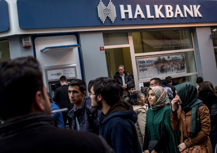 Image: People walk past a branch of the Turkish Halk Bank