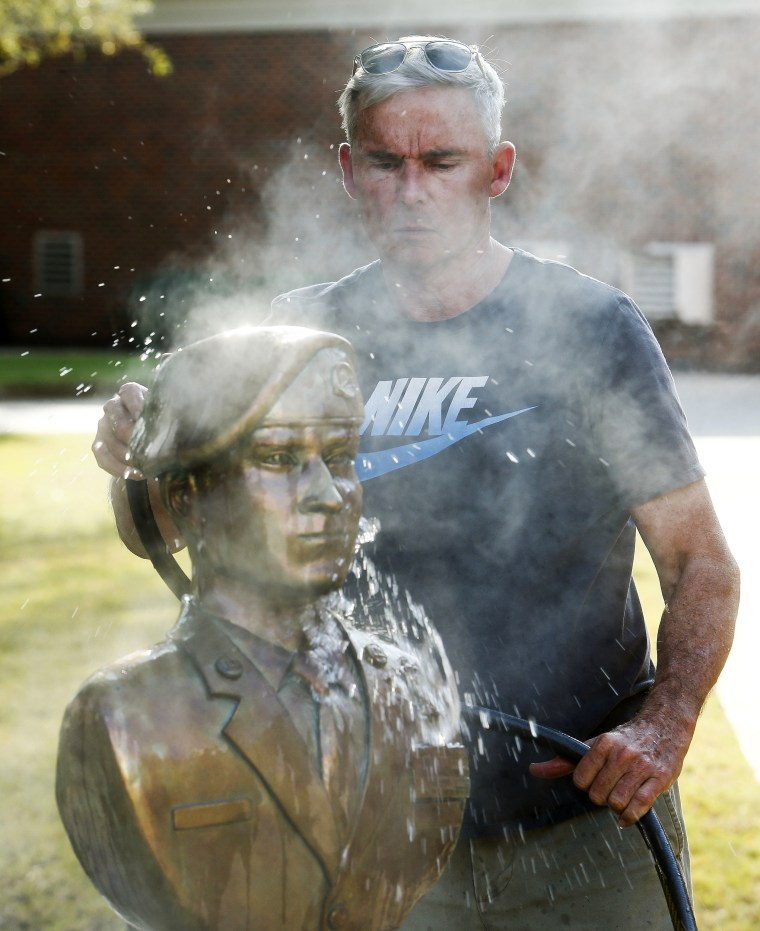 Image: Sculptor Lee Busby uses a water hose to cool the image of Mark Forester he sculpted