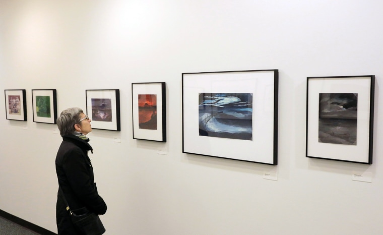 """Image: A woman looks at paintings made by detainees at military facilities in Guantanamo Bay at the """"Ode to the Sea: Art from Guantanamo Bay"""" exhibition in New York"""