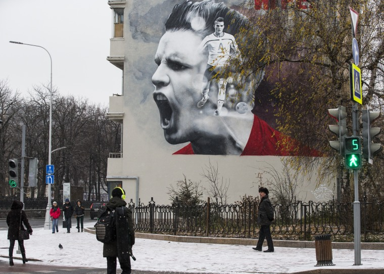 People walk past a huge poster promoting the upcoming soccer World Cup 2018 tournament in Moscow, Russia, Tuesday, Nov. 28, 2017. The World Cup will be played at 12 stadiums in 11 Russian cities.