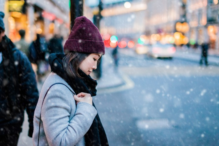 Image: Young Asian walking on the street under snow