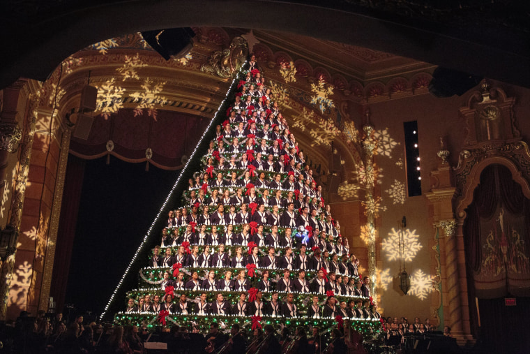 Image: Members of the Mona Shores High School Choir stand in the Singing Christmas Tree