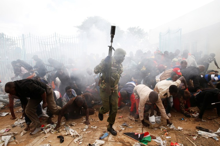 Image: Police fire tear gas to control a crowd of supporters as they try to force their way into the inauguration of President Uhuru Kenyatta