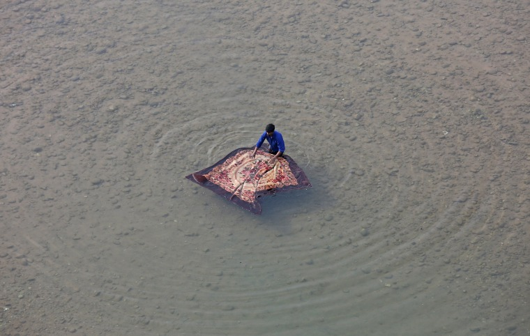 Image: A man washes a blanket on the banks of the Tawi River in Jammu