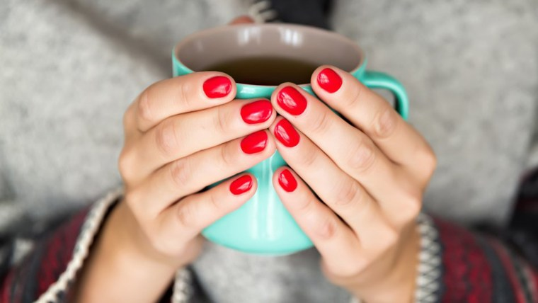 woman's hands with red nails holding mug