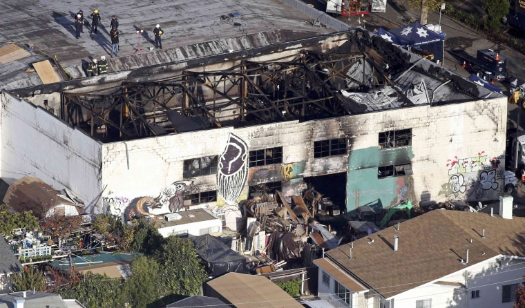 Image: Recovery teams examine the remains of the warehouse that caught fire in Oakland