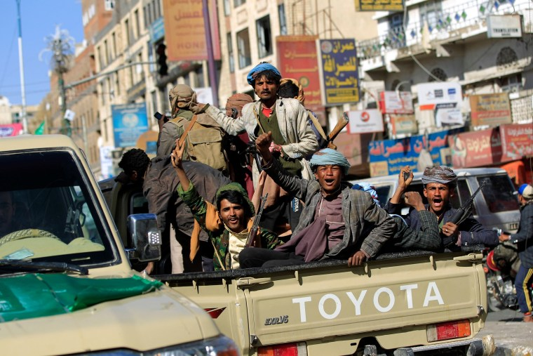 Image: Houthi rebel fighters ride an armored vehicle