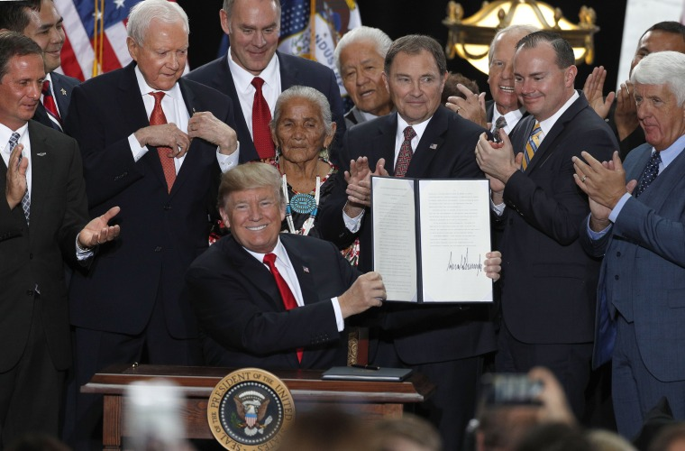 Image: With Utah officials surrounding him, President Donald Trump shows an executive order he signed reducing the Grand Staircase-Escalante National Monument