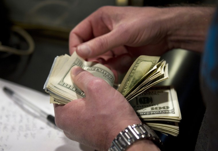Image: A man counts out $100 bills as he makes a bet on Super Bowl XLVIII in Las Vegas
