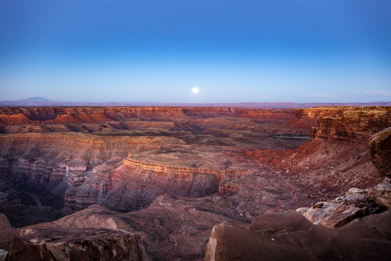 Image: A full moon sets behind Cedar Mesa, which is within Bears Ears National Monument, near Mexican Hat