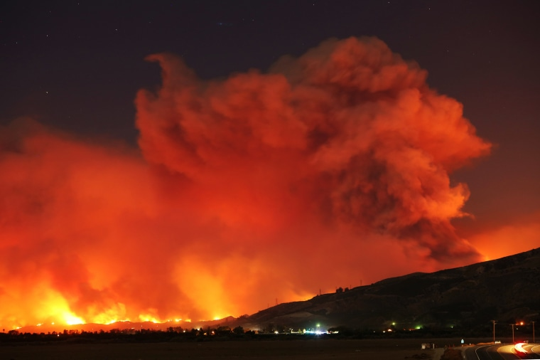 Image: Smoke rises into the night sky as strong winds push the Thomas Fire across thousands of acres near Santa Paula