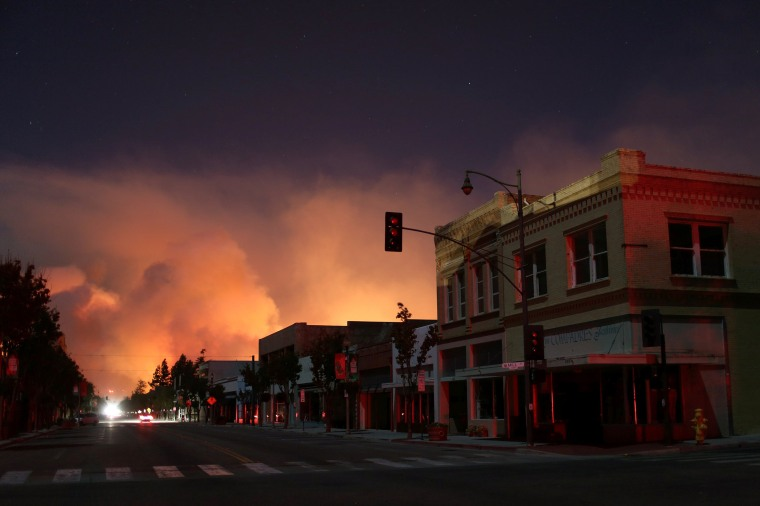 Image: Downtown is darkened by a power outage with smoke rising in the distance as strong winds push the Thomas Fire across thousands of acres in Santa Paula