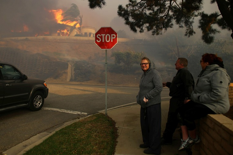 Image: Neighbors watch as a house burns during a wind driven wildfire in Ventura, California