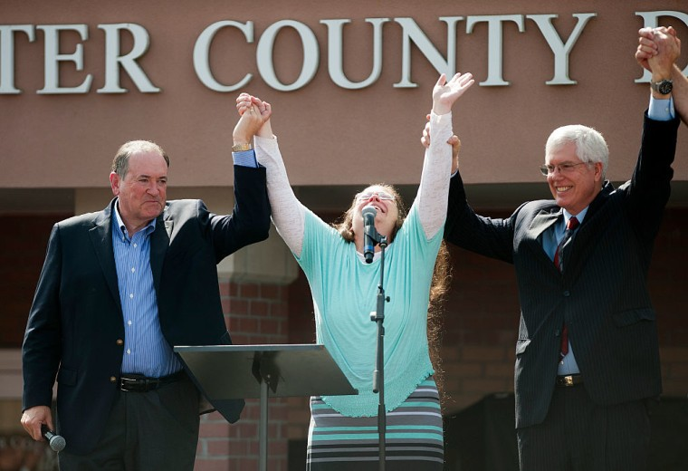 Rowan County Clerk Kim Davis holds her hands in the air with her attorney Mat Staver (R) and Republican presidential candidate Mike Huckabee in front of the Carter County Detention Center on September 8, 2015 in Grayson, Kentucky.