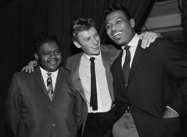 This file photo taken on October 20, 1962 shows US pianist and singer-songwriter Fats Domino (L) being congratulated by French singer Johnny Hallyday (C) and US boxing champion Ray Sugar Robinson following his performance at the Palais des Sports in Paris.