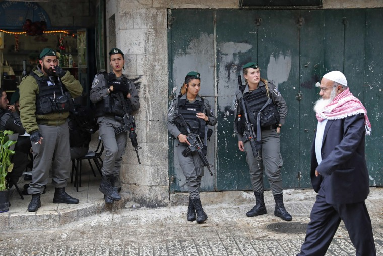 Image: A Palestinian man walks past Israeli border guards in Jerusalem's Old City