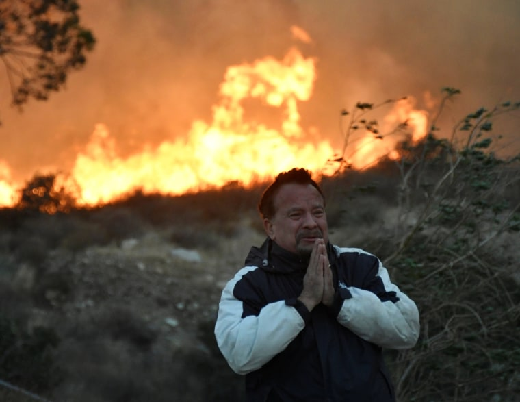 Image: A local man tries to cope and prays during an early-morning Creek Fire that broke out in the Kagel Canyon area in the San Fernando Valley north of Los Angeles