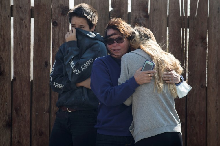Image: Local residents react as numerous homes burn on a hillside during a wind driven wildfire in Ventura, California