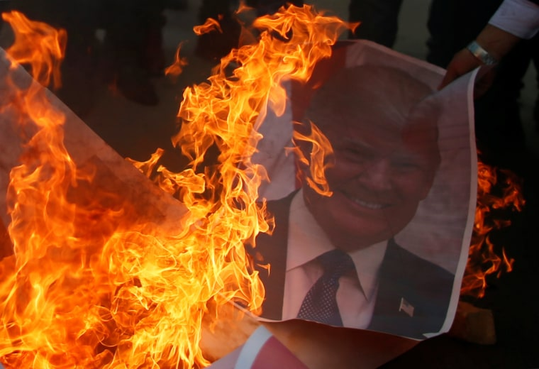 Image: A Palestinian protester burns a poster of U.S. President Donald Trump in Gaza City Thursday.