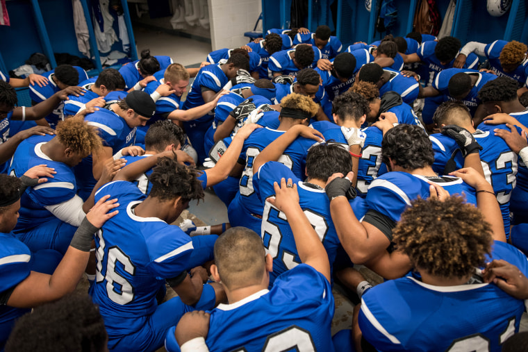 Image: The C.E. King Panthers pray in the locker room before the big game