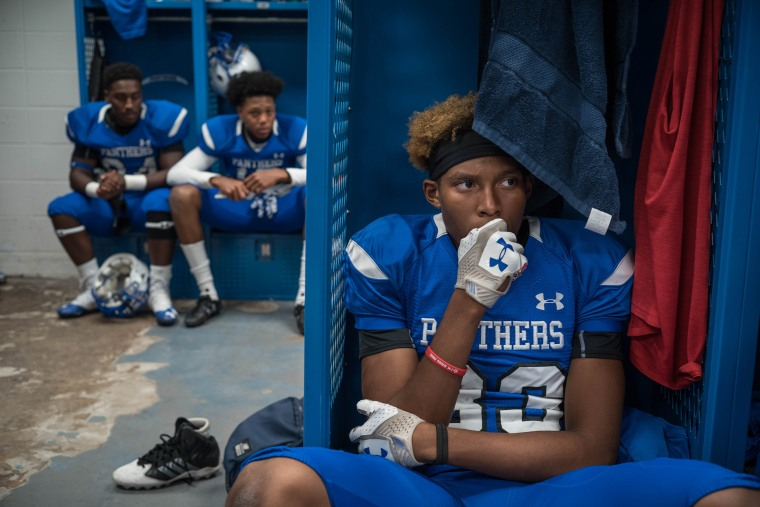 Image: C.E. King's Christian Sanchez, right, waits the start of the game in the locker room