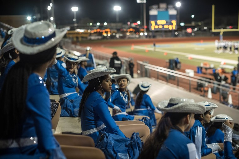 Image: Members of the C.E. King's drill team wait in the stands before the start of the game