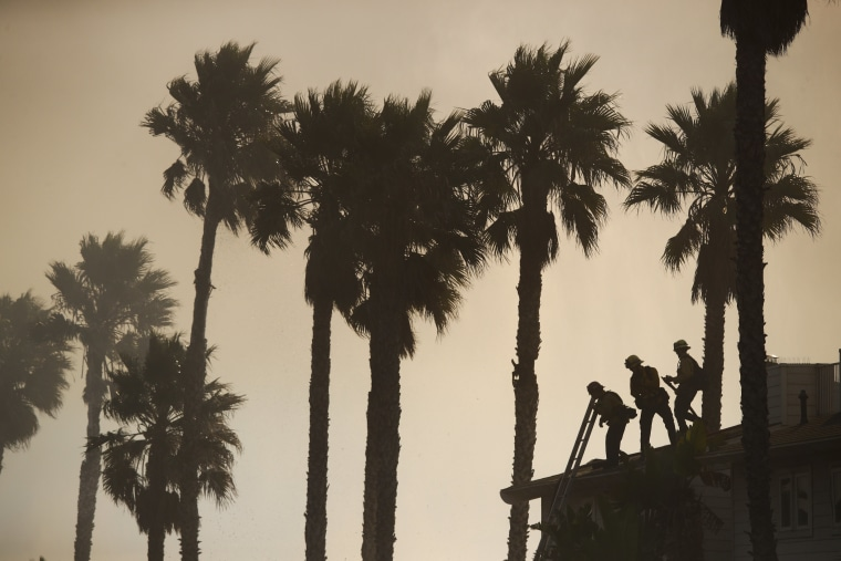 Firefighters stand on the rooftop of a beach house to water down the property while battling a wildfire at Faria State Beach in Ventura, on Dec. 7.