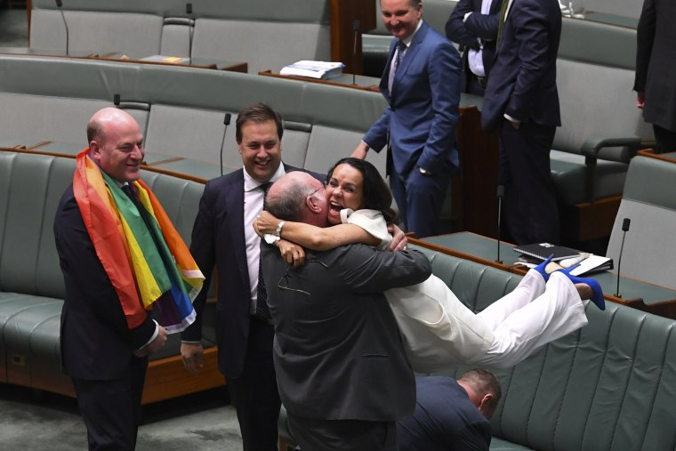 Image: Liberal MP Warren Entsch lifts up Labor MP Linda Burney as they celebrate the passing of the Marriage Amendment Bill in the House of Representatives at Parliament House in Canberra