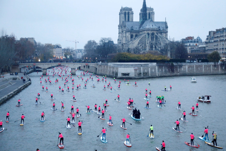 Image: Participants take part in the 8th Edition of the Nautic SUP Paris Crossing stand up paddle competition near the Notre Dame Cathedral on the river Seine in Paris