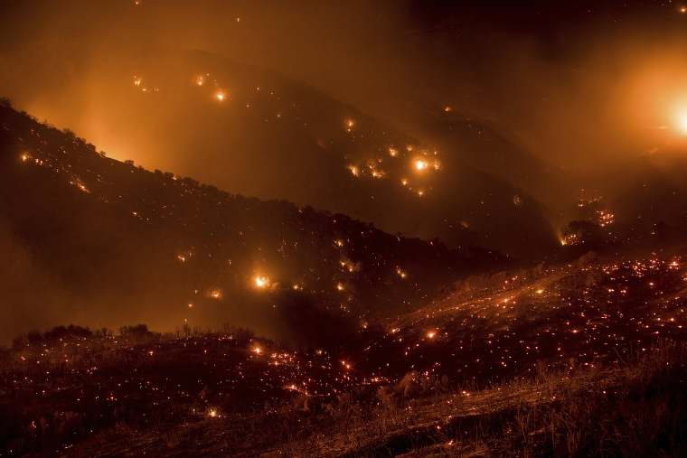Image: A hillside glows with embers as the Thomas fire burns through Los Padres National Forest