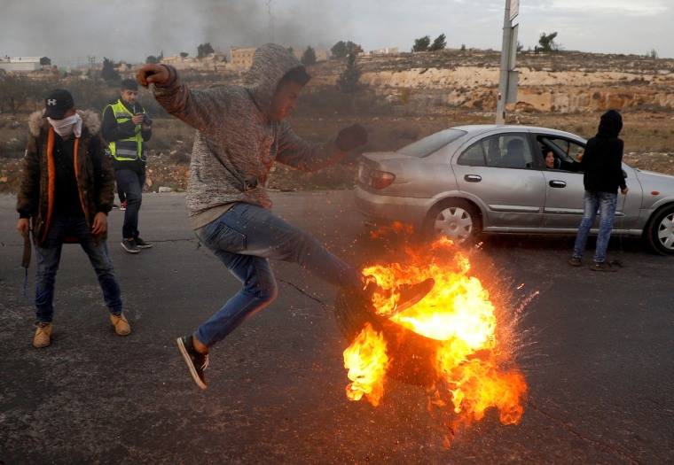 Image: A Palestinian kicks a burning tire during clashes with Israeli troops at a protest against U.S. President Donald Trump's decision to recognize Jerusalem as Israel's capital, near the Jewish settlement of Beit El, near the West Bank city of Ramallah