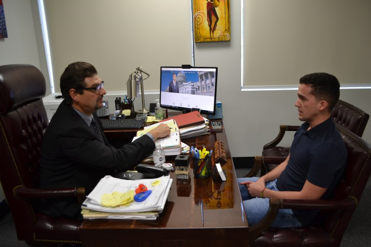 Miami immigration attorney, Angel Leal, speaks with his client, Gino Castellanos. Because of the withdrawal of U.S. personnel from the U.S. Embassy in Havana, his wife is now waiting for the interview date at the embassy in Bogota, Colombia.