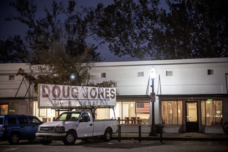 Image: A sign in support of U.S. Senate candidate Doug Jones (D), Moore's opponent, hangs on a pick up truck outside of OK Bicycle Shop in Mobile.